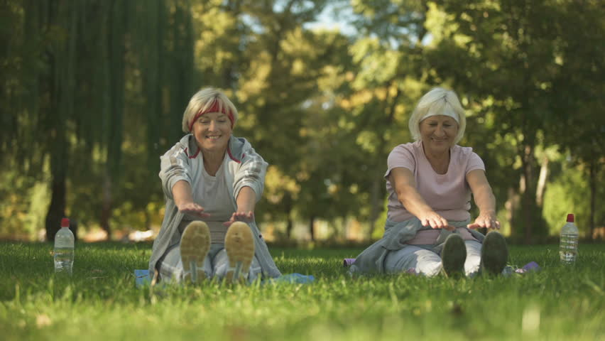 Middle and elder age women doing exercise in park, stretching their bodies | Shutterstock HD Video #1023108856