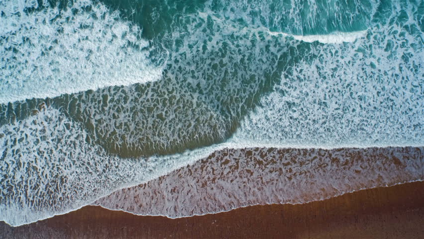 Aerial drone slow motion footage of ocean waves reaching shore. Lockdown shot of sea waves creating a texture from the white sea foam. Footage is filmed from an overhead perspective. HD 1080 video. #10231106