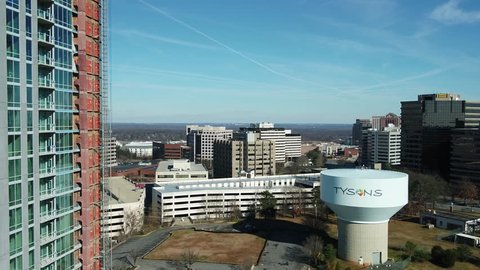 Tysons, VA / USA - December 29 2018: Descending showing Tysons water tower with newly-constructed skyscraper in left of frame