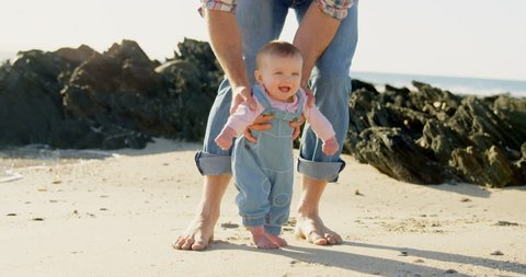 Front view of mid adult Caucasian father helping baby to walk at beach on a sunny day. Baby learn to walk