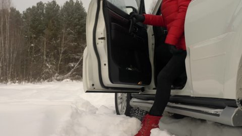 Feet girl that goes out of the white car winter outdoors. Red shoes footwear. Red clothes. Women legs come out from car door. Low angle