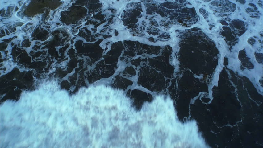 Aerial drone footage of huge waves rushing rocks. Tracking shot of tidal waves crashing. As the powerful waves break they create a texture from white sea foam. Overhead perspective. HD 1080 video.