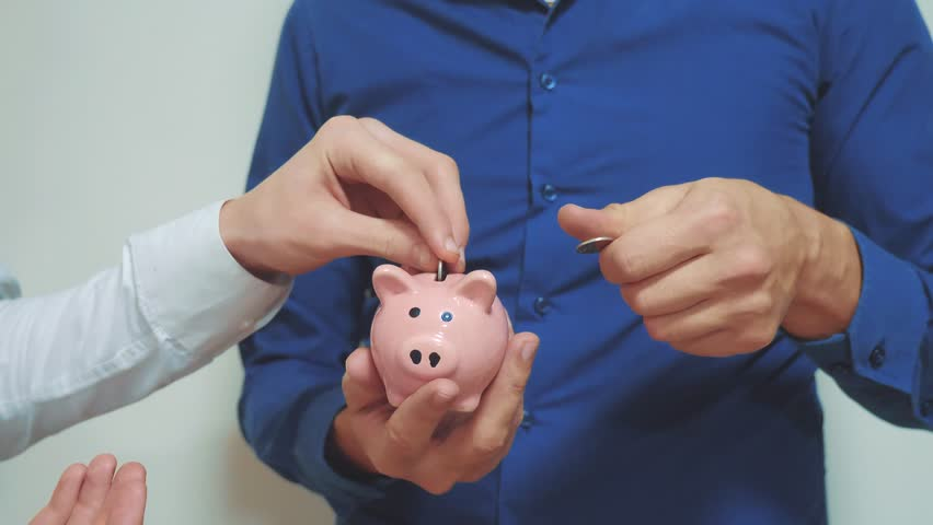two businessmen teamwork makes savings puts coins in a piggy bank. two men piggy bank business concept. slow motion video. saving money is an investment for the future. Banking investment and finance