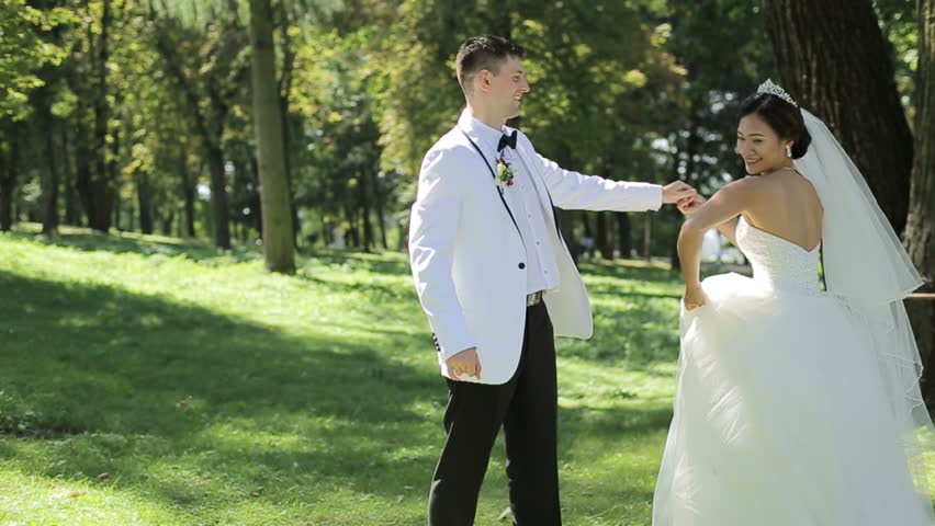 Asian Bride and groom in love at beautiful green forest. Happy moments. Groom spins bride in white dress | Shutterstock HD Video #1023186106