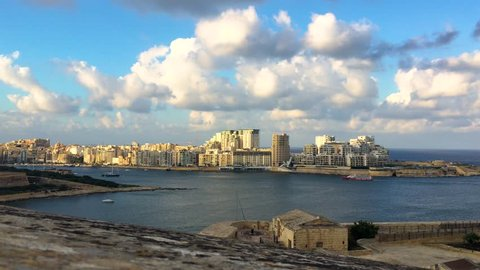 Timelapse white clouds passing over Sliema, Malta on a sunny day. Filmed from the walls of Valletta.