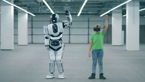 Human-like cyborg is lifting his arms after a boy in VR-glasses