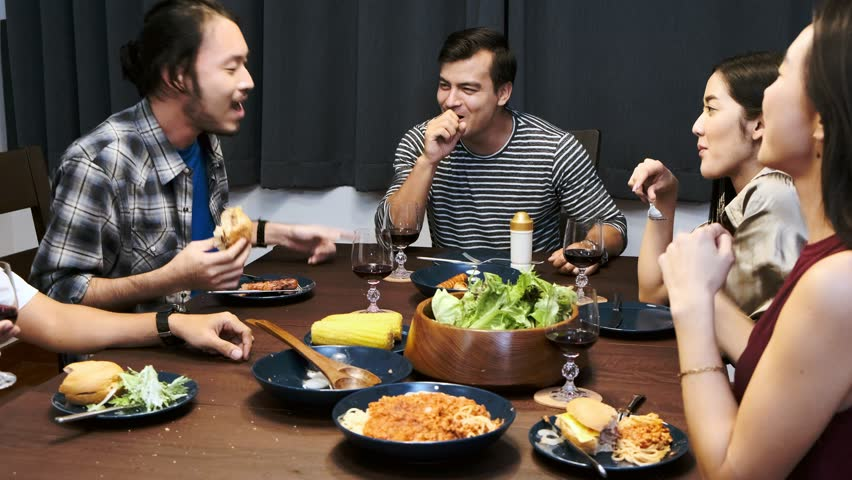 Friends having dinner in a house party. Mixed race young people enjoying dinner and wine together, laughing together and eating burger. House party concept. | Shutterstock HD Video #1023241156