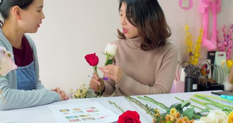beautiful young woman florist teaching her friend making a bouquet, young woman holding daisies and smiling, in chengdu china