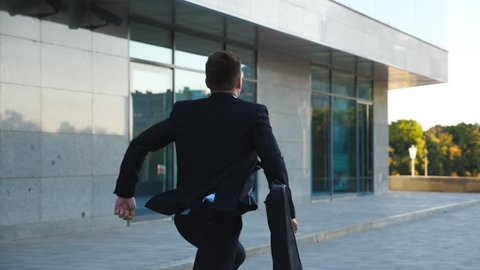 Unrecognizable businessman with briefcase runs down city street. Business man late for meeting. Successful man in suit jogging near modern building. Guy in hurry to appointment. Back view Slow motion