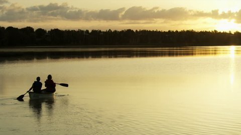 Silhouette of healthy senior Caucasian European couple outdoors in the canoe on the lake paddling and enjoying the sunset RED WEAPON