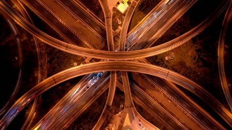 Aerial drone night time lapse or hyper lapse high speed video of multilevel junction highway crossing during rush hour with heavy traffic