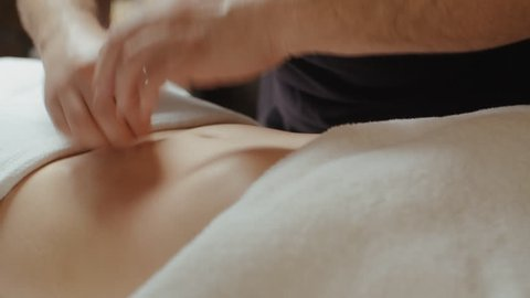Male masseur doing stomach anti-cellulite massage. Young slim woman receiving rejuvenation procedure in spa salon, relaxing lying on massage table slide camera