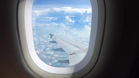 Beautiful cloud and wing of airplane from window with a nice blue sky
