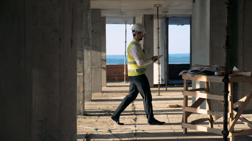 Male worker types on a tablet, walking in a building, side view. | Shutterstock HD Video #1023304036