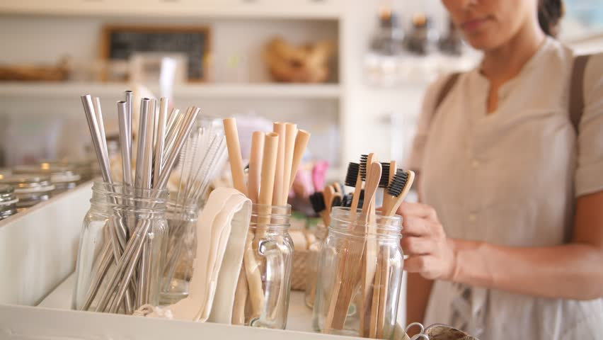 Young Mixed Race Woman Choosing Bamboo Eco Friendly Biodegradable Toothbrush in Zero Waste Shop. No plastic Conscious Minimalism Vegan Lifestyle. Reduce Reuse Recycle 4K Slowmotion Concept. | Shutterstock HD Video #1023335146