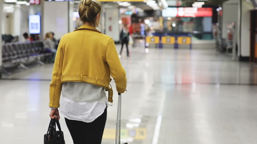 Back shot of young woman in yellow leather jacket walking through airport. Girl in fashionable clothes with hand luggage. Passenger, vacation concept.