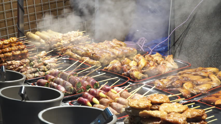 4k Video footage point of view shot a lot of grilled barbecue in warming pans. BBQ meat, bacon, chicken wing, sausage, meat, pork and vegetables. Street food at traditional market in Taipei, Taiwan.   Shutterstock HD Video #1023375436
