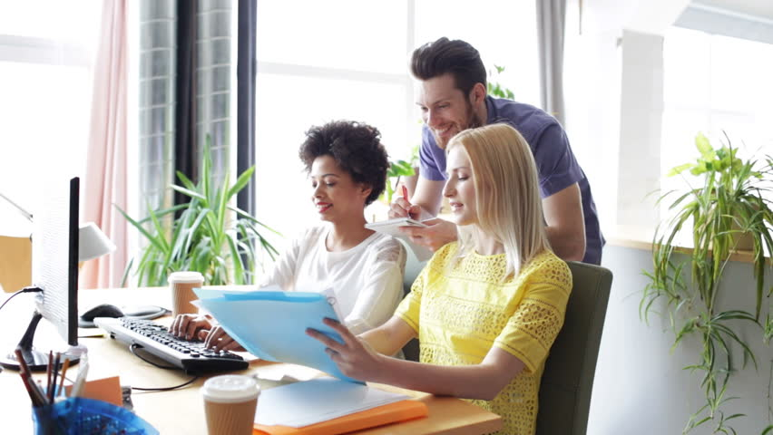 Business, startup and people concept - happy creative team with computers and folder discussing project in office   Shutterstock HD Video #10233791