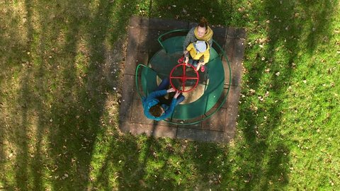 Aerial view of family pointing to drone at merry-go-round, Zagreb, Croatia.