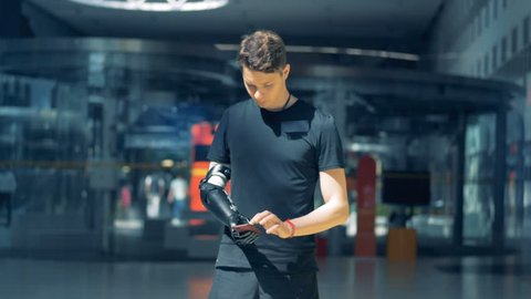 One person holds a phone with his cybernetic prosthesis, working with it. Cyborg concept.