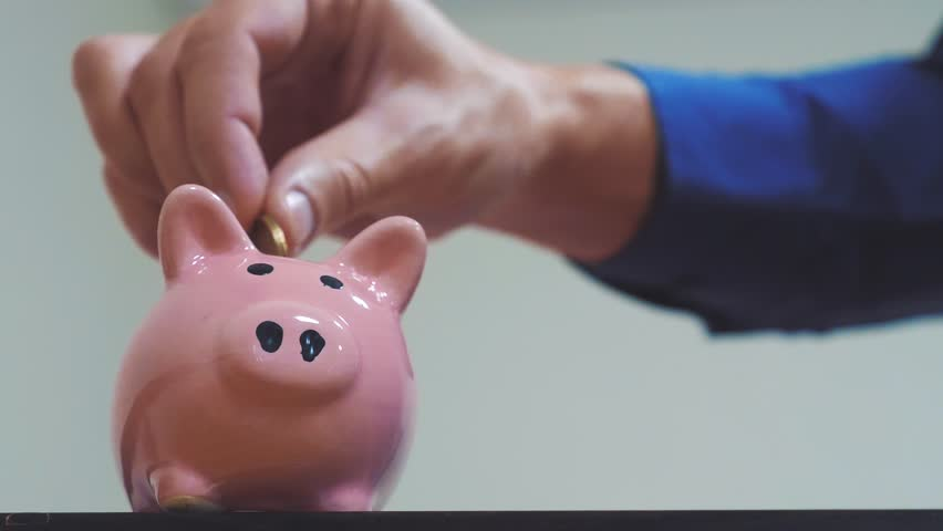 businessman makes savings puts coins in a piggy bank. piggy bank business concept. slow motion video. saving money is an investment for the future lifestyle. Banking investment and finance. hand is