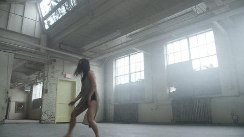 Dancer freesyling in industrial warehouse. Filmed with RED Dragon 6K camera