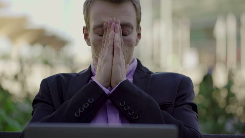 Tired businessman taking off glasses and looking at laptop. Exhausted young blond man working with laptop at park. Overwork concept | Shutterstock HD Video #1023452746