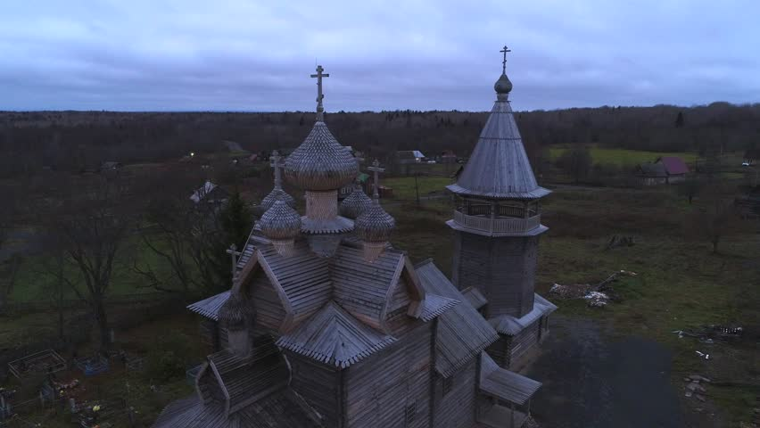 View of the old wooden Church of St. Dimitri Solunski in the evening of the November (aerial video). Village Shcheleyki, Leningrad region, Russia