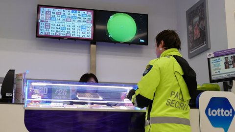 Coquitlam, BC, Canada - January 28, 2019 :  Motion of security guard buying lottery ticket inside mall lottery ticket retailer with 4k resolution.
