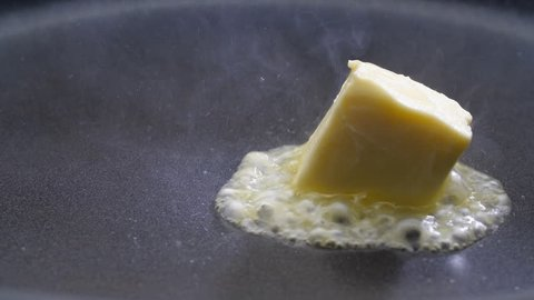 Butter melting sizzling in frying pan on stove. Close up.