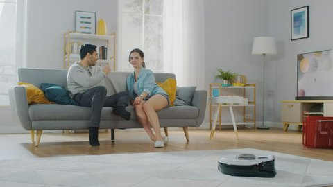 Shot of a Smart Robot Vacuum Cleaner Sucking Up Dust from a Carpet. Beautiful Couple is Sitting on a Sofa and Talking in the Background. Technological Home Appliance Device Moves Past Them.