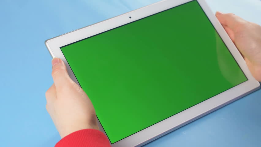 Woman in red sweater hold tablet with green screen on blue pastel surface. Close up top view 4K footage. #1023559186