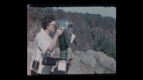 1955 Glam 50s woman peers through coin operated binoculars at Viewpoint