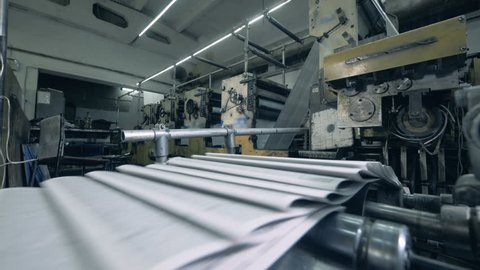 Printing press is releasing folded pages of paper