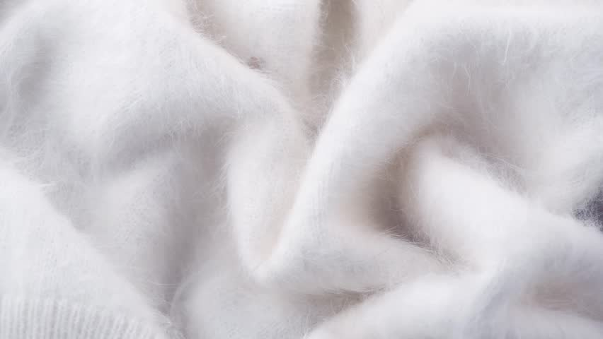 Wool background. Alpaca wool mohair clothes texture closeup. Natural Cashmere Soft and fluffy merino wool macro shot. Woolen fabric. Knitted hairy detail texture surface Rotated. 4K UHD video slowmo | Shutterstock HD Video #1023636046