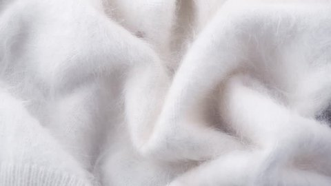 Wool background. Alpaca wool mohair clothes texture closeup. Natural Cashmere Soft and fluffy merino wool macro shot. Woolen fabric. Knitted hairy detail texture surface Rotated. 4K UHD video slowmo