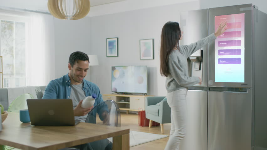 Beautiful Young Woman Opens the Fridge and Gives a Milk Bottle to Her Boyfriend. Then She Checks the Futuristic Digital To-Do List on the Smart Fridge Door. | Shutterstock HD Video #1023697426
