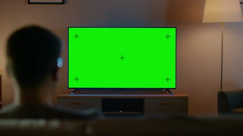 Young man in glasses is sitting on a sofa and watching tv with horizontal  green screen mock up  it's evening and room at home has working lamps