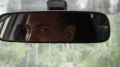 Young Caucasian Man Driving Car and Wink Flirting with Passenger Looking in Rear View Mirror