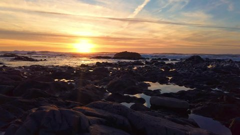 Long duration sunset over ocean and rocky shore