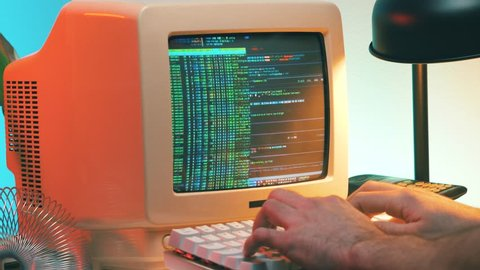 Hacker in the 80s 90s hacking a computer retro style. He even takes his vintage phone.