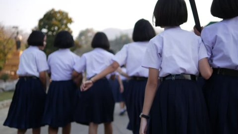 High school students are walking towards preparing to respect the national flag in the morning amidst the beautiful nature surrounding the school in Thailand, Southeast Asia.