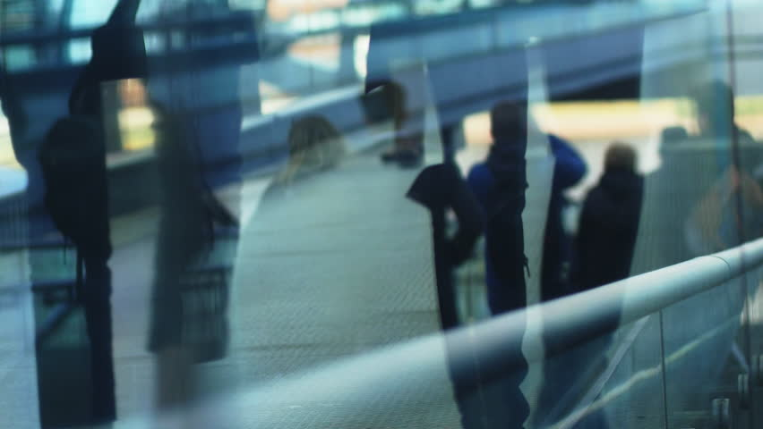 People walking through glass reflection. Business people going to offices in slow motion. 4k Video different colors and style in the gallery