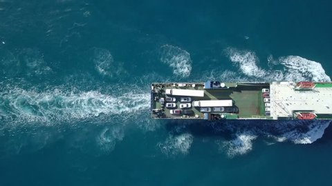 Medium sized Ro-Ro (Roll on/off) ship roaring across The Mediterranean Sea with cars and trucks seen on the upper deck.