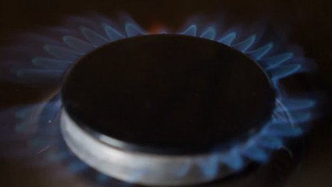 Natural gas inflammation in stove burner. Slow motion. Turns on gas stove burners. ignition of blue gas from the burner gas kitchen stove. The tips of the flames painted different colour. hd