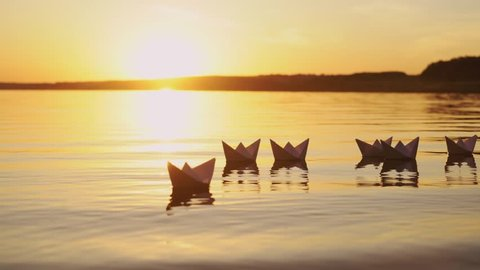 Many nice homemade paper boats floating in the river with a beautiful sunset background. Ships made from paper swimming on the water surface in the evening