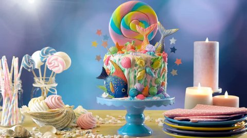 On trend mermaid ocean theme candy land fantasy drip novelty cake for children's, teen's, novelty birthday and party celebrations, color background, purple bokeh background.