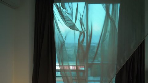 Curtain fluttering in the wind at the window. Wind at the window. Breath of wind. Open window.
