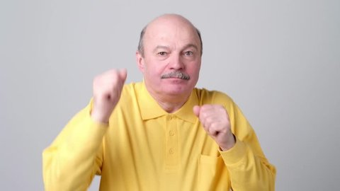 Expressive old man in yellow shirt dancing on birthday party. He got promotion or is retired now, has a vacation