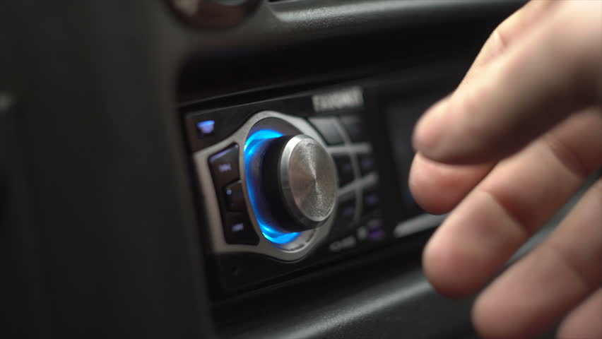 Men Switches And Listens The Radio In The Car
